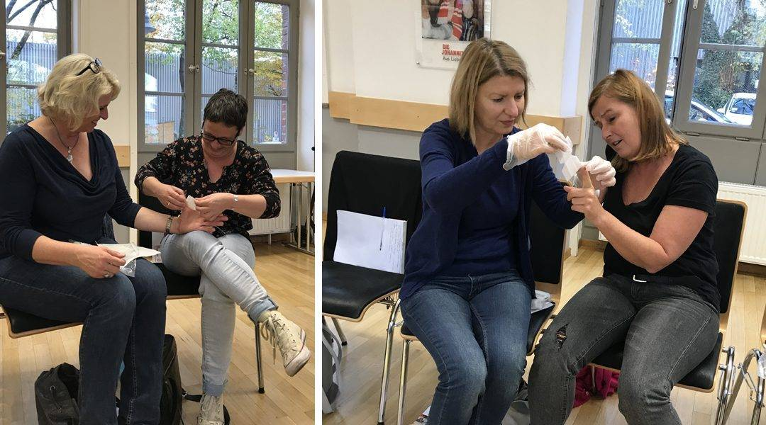 Nicole und Andrea bei der professionellen Wundversorgung, Erika legt Sabine einen Fingerkuppenverband an.
